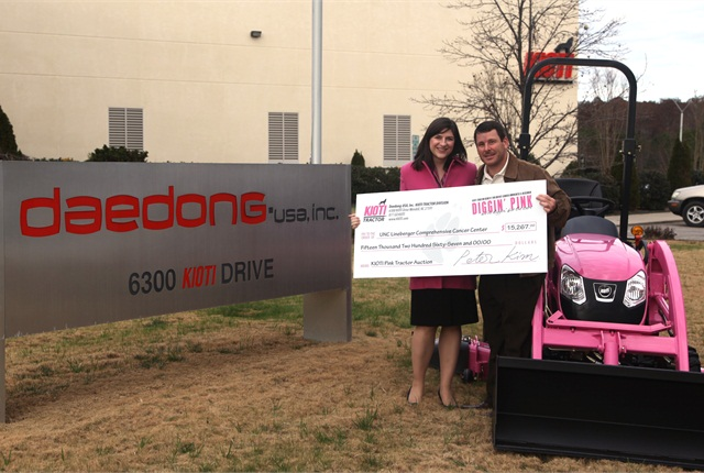 Douglas Earwood, Director of Sales, Presents Pink Tractor Auction Proceeds Check to Jennifer Bowman, Special Events Coordinator of UNC Lineberger.
