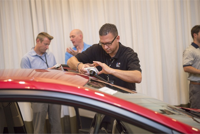 Rich Perkowski, field remarketing manager at BMW Financial Services, takes picture of vehicle at Manheim's Client Advisory Board (CAB) meeting. (PHOTO: MANHEIM)
