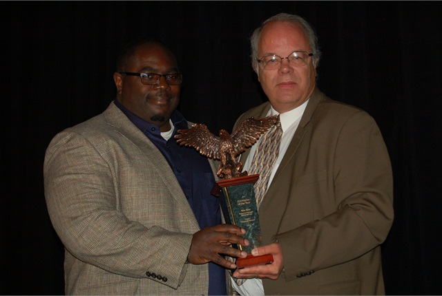Mike Reid (left) of Toyota Financial Services accepts the 2014 Consignor of the Year Award from Automotive Fleet Editor Mike Antich.